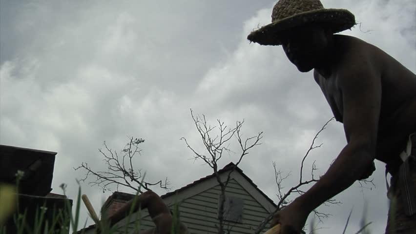 VIRGINIA - 2014. Re-enactment recreation of 1700-1800s Southern American Slavery, slave era. Enslaved African-American. Working in field, praying, laboring in bondage. tattered clothing, Field slave.