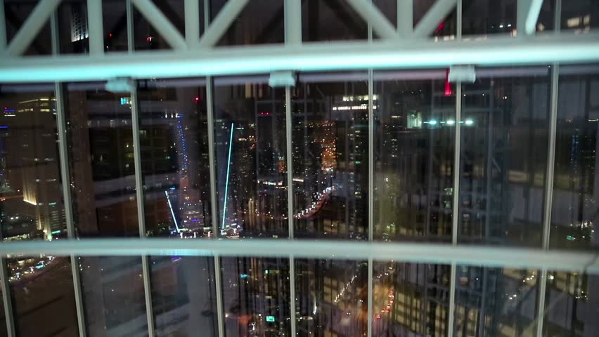 View from glass elevator at night, Dubai, United Arab Emirates. Elevator goes down. Dubai is a city and emirate in the UAE. The emirate is located south of the Persian Gulf on the Arabian Peninsula