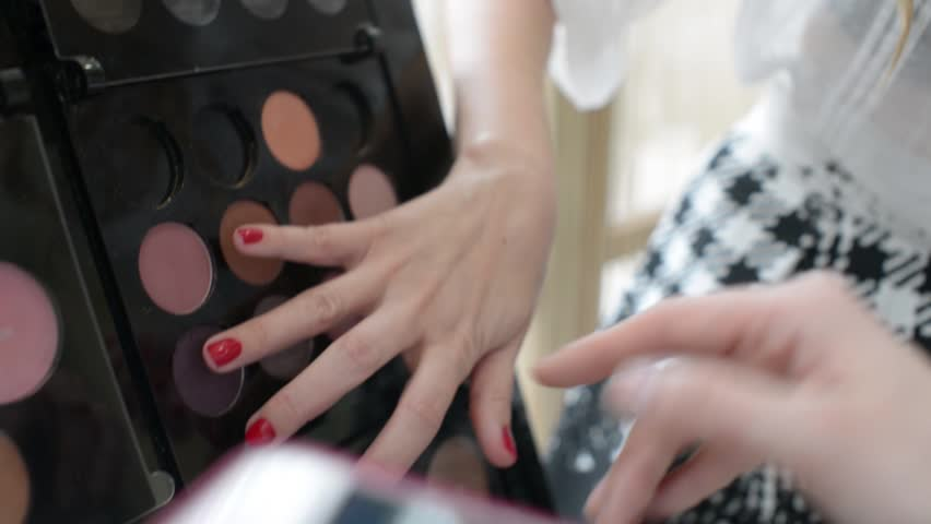 Rack with lipsticks and shadows - make-up artist and stylist choose cosmetics for the client in the beauty salon