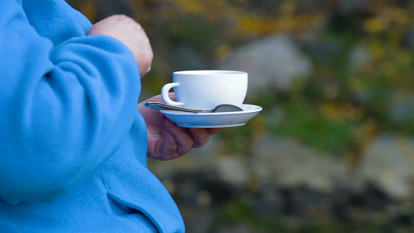 senior woman hands holding white coffee cup outdoors Differential Focus, Unrecognizable Person,  Side View