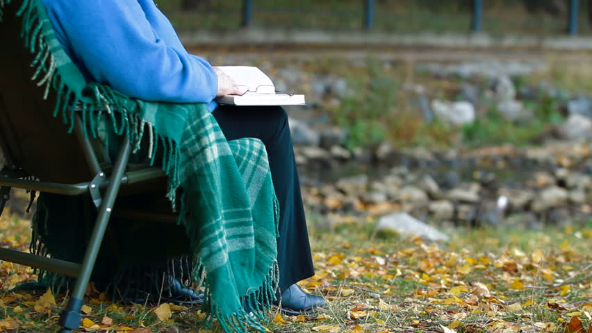 Senior woman enjoying  Retirement with a book at autumn park by the river Unrecognizable Person,  Side View