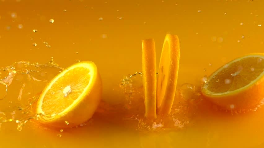 Cut ripe orange hits orange juice surface and rebounces. Slow motion video