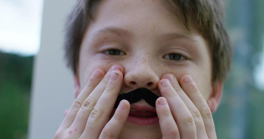 4K Close up portrait of little boy wearing false moustache poking out his tongue. Shot on RED Epic.