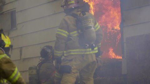 Huge flames billow from the door of a house with firefighters ride outside