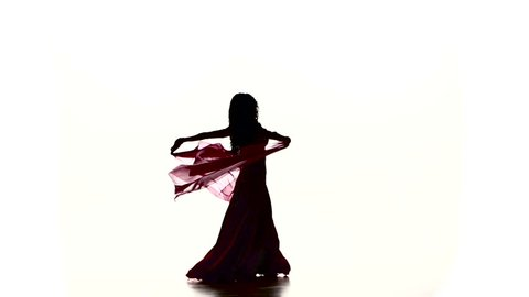 Pretty young girl starts dancing belly dance with colored shawl, on white, slow motion