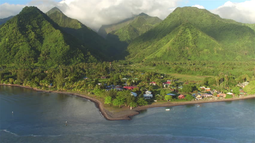 4K AERIAL: Flying from ocean lagoon towards beautiful exotic Tahiti island with big volcanic mountains, lush rainforest jungle and small fishing village on the beach