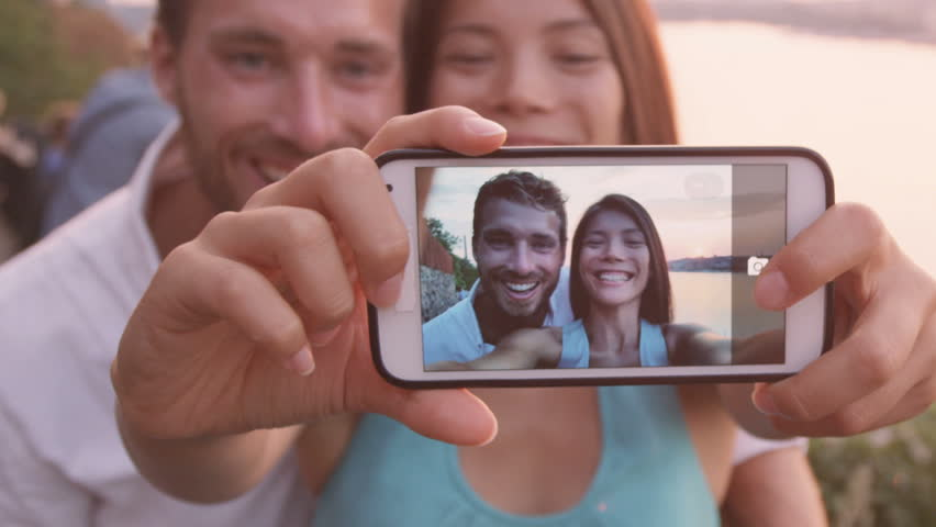 Smart Phone Selfie - Couple Taking Self Portrait Using Smartphone Camera.  Dating Couple In Love Having Fun Taking Candid Fresh Picture Photo Laughing  ...