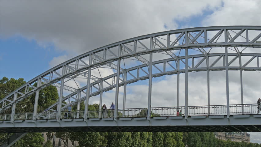 The metal bridge with a lake underneath. The metal bridge with cars and people passing by #15167779