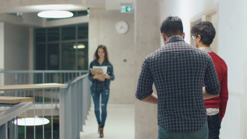 Young male and female students accidentally bump into each other in a college hallway. Shot on RED Cinema Camera in 4K (UHD).