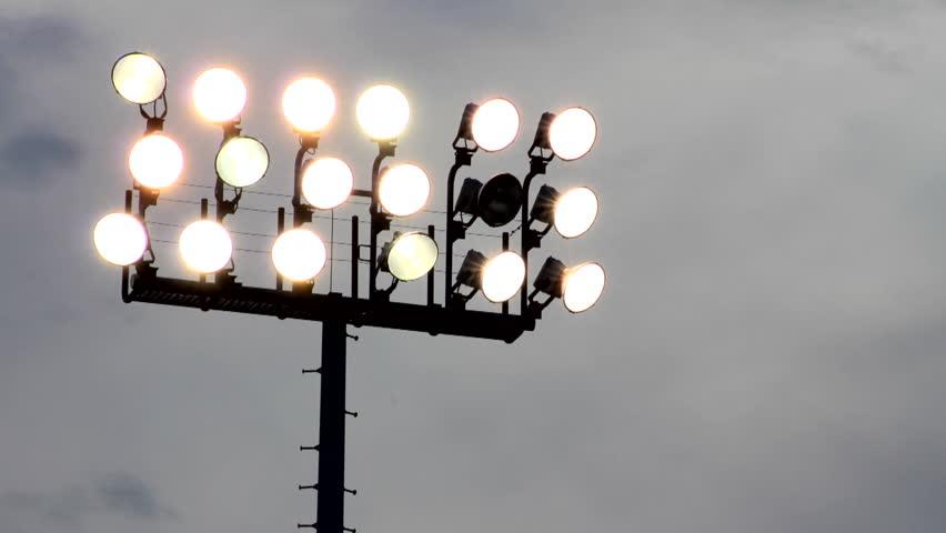 Time-lapse of clouds behind broken stadium lights.