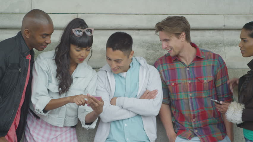 4K Portrait of happy mixed ethnicity group of friends looking at smartphone outdoors | Shutterstock HD Video #15184168