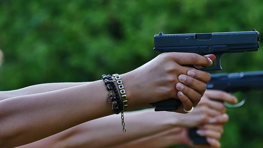 Gun shooting range two guns glocks/beretta close up shooting the same time. slow motion sexy girls having fun on shooting range. Military lifestyle, militia training. Girls guns and rock n roll.