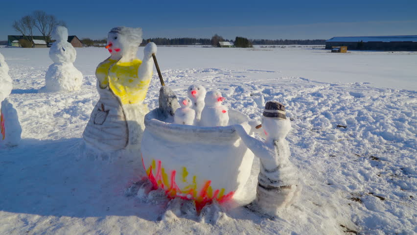 Some of the snow sculptures on the ground. There are snowman and other figures found in the field