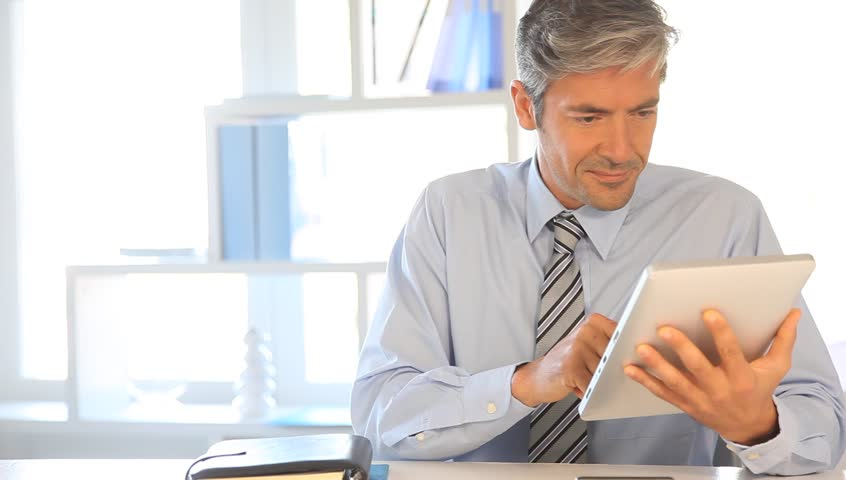 Man in office using electronic tablet