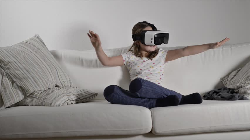 Girl wearing virtual reality goggles. Studio shot, white couch    Shutterstock HD Video #15240400
