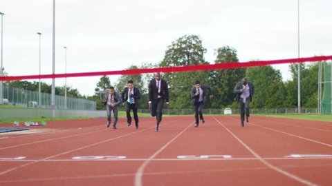 4K Group of competitive businessmen racing to the finish line at running track