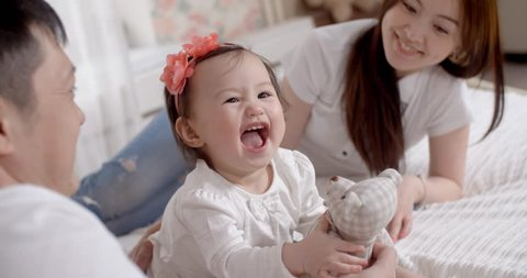 family idyll,a young Asian family with two daughters, a fun play at home on the bed with the baby 1 year, slow motion