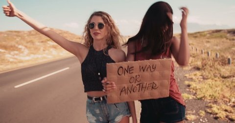 Caucasian girl and mixed race hipster girl in the daytime stand on side of two lane highway hitchhiking while holding cardboard sign with the One Way or Another written on it and sticking out thumb