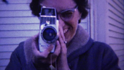 MORTON, ILLINOIS 1961: 60's style eyeglasses women filming 8mm movie camera.