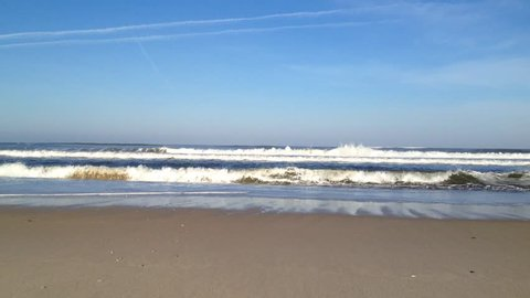 Beautiful beach with ocean sea crashing rolling waves under a blue sky with white clouds, rip currents.