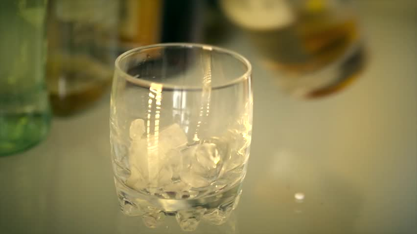 Shot of Puring alcoholic drink into glass