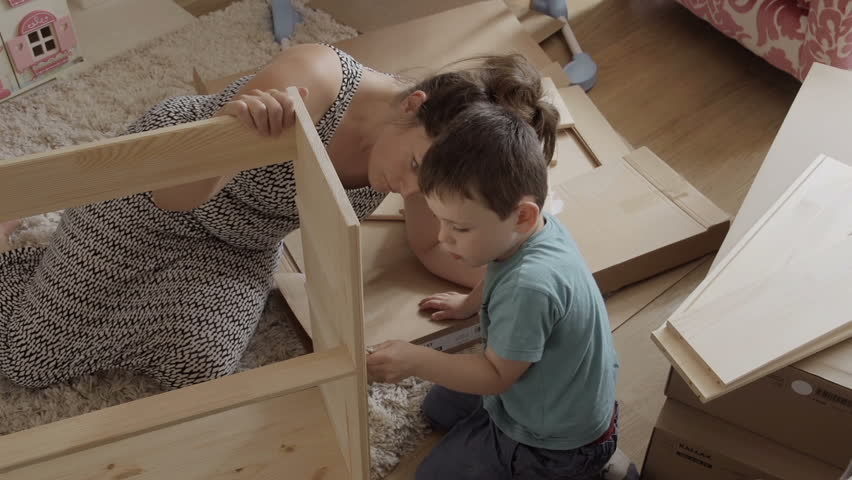 Mother and son assembling flat pack draws do it yourself stock single mother teaching her young son how to assemble a flat pack kit hd stock solutioingenieria Image collections