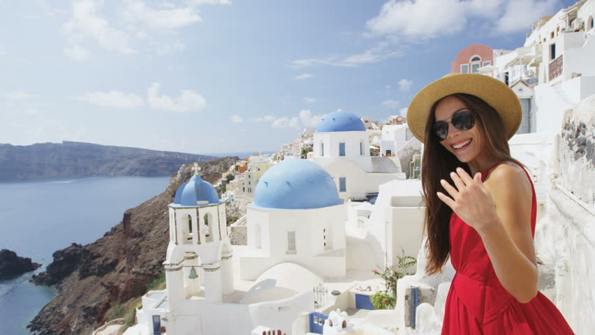 Woman welcome you to walk with her on Santorini. Female tourist is enjoying summer vacation travel showing welcoming gesture smiling happy. Traditional typical Oia village, Santorini, Greece, Europe.