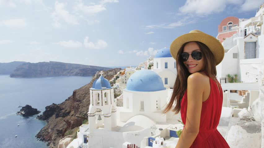 Beautiful young woman enjoying her vacation On Santorini. Happy tourist is wearing sunhat, sunglasses and red dress standing by traditional whitewashed buildings, Oia, Santorini, Greece, Europe. | Shutterstock HD Video #15325111