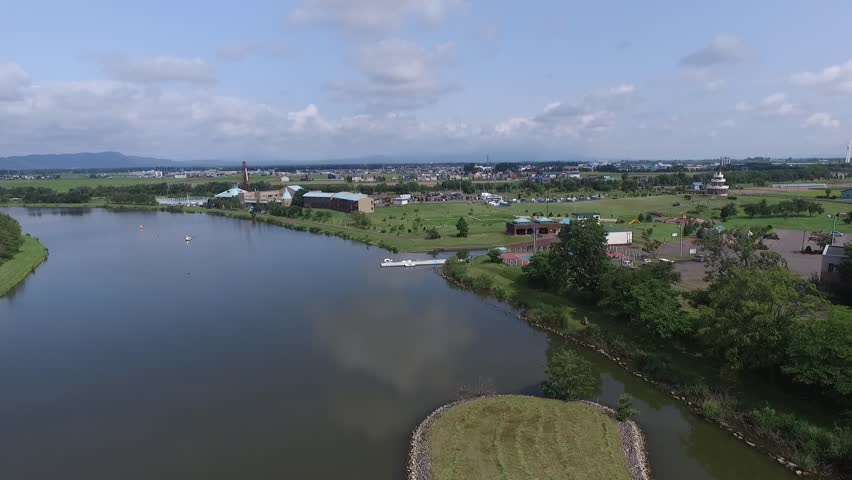 Aerial: river landscape surrounded by the summer of blue sky and green _4 / In the summer of 2015 shooting in Hokkaido, Japan / River and green flowing to the vast plains   Shutterstock HD Video #15325549
