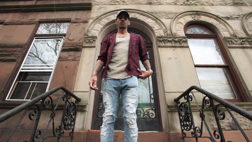A young man walks out of his Brooklyn brownstone home.
