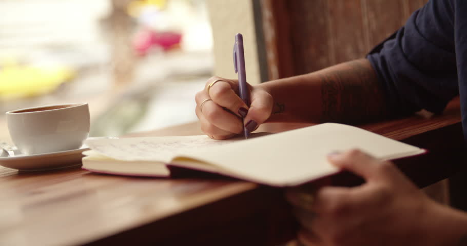Close up of a Woman sitting and writing in her journal in busy coffee shop | Shutterstock HD Video #15332734