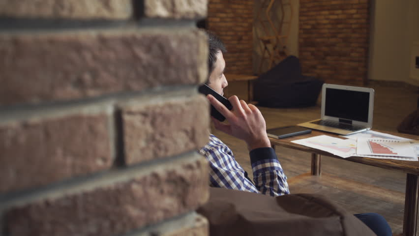 A man in a coworking sitting talking on the phone on the table notebooks documents. Soft panorama | Shutterstock HD Video #15352639