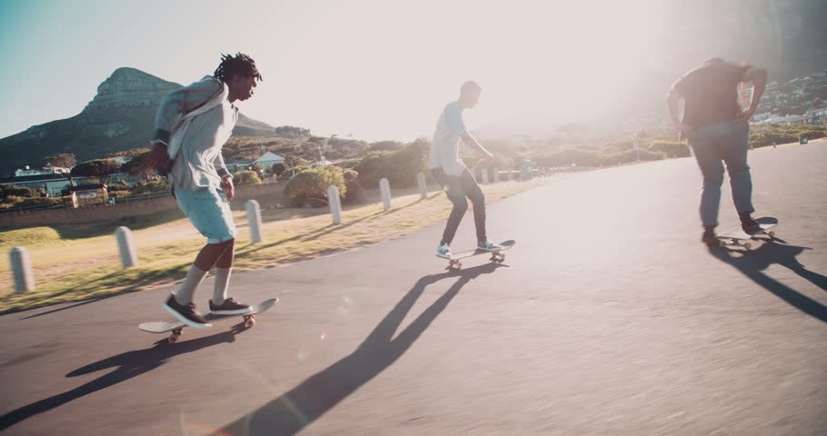 Multi-Ethnic group of skater friends skateboarding down road at seaside together during sunset