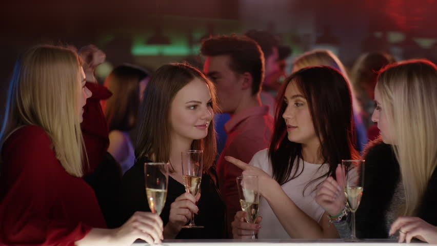 Four attractive girls at bar in club with champagne glasses smiling | Shutterstock HD Video #15364399