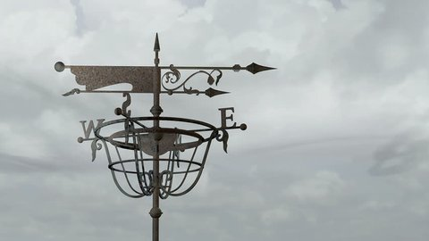 the old iron weather vane spinning in the background windy sky with clouds