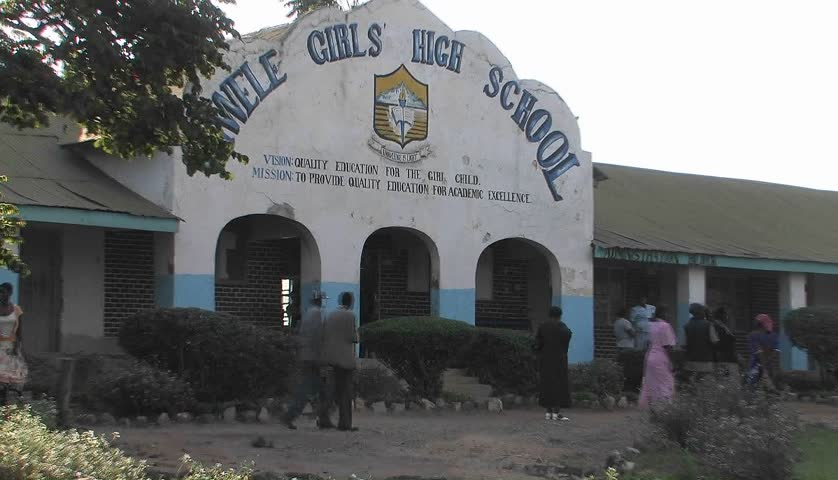 KENYA, AFRICA - CIRCA 2009: People walk past a high school in Africa circa 2009 in Kenya.