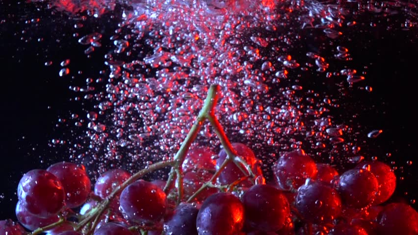 Bunch of red grapes falling into water close up super slow motion shot
