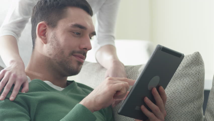 Happy couple is sitting on a sofa at home and using a tablet computer. Shot on RED Cinema Camera in 4K (UHD).