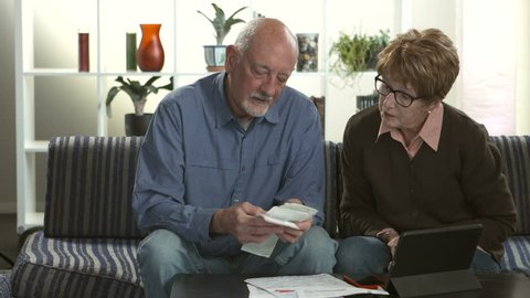 A senior couple stressed over paying bills