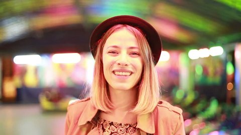 Close up of beautiful blonde girl in hat looking at camera, smiling and winking in amusement park