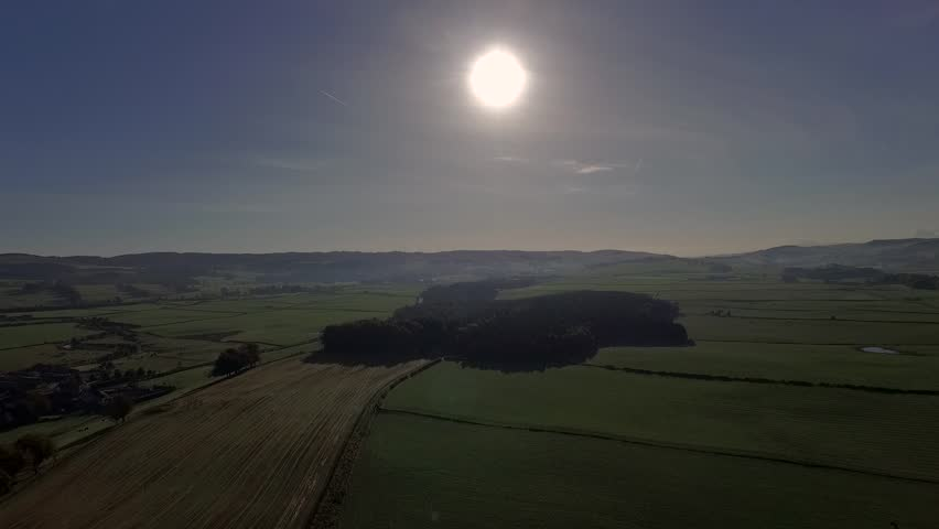 Aerial view of British countryside in the morning sun with blue sky