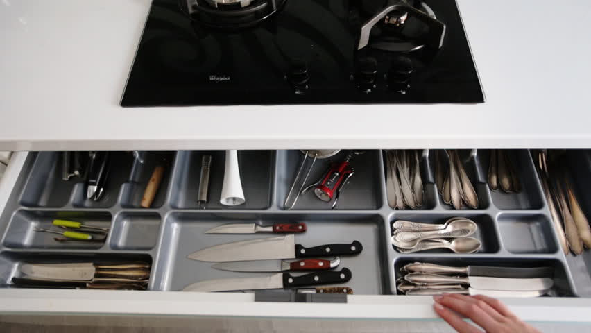 Close Up Of Female Hands Opening Kitchen Cabinet Door And Taking The Biggest Knife From Their