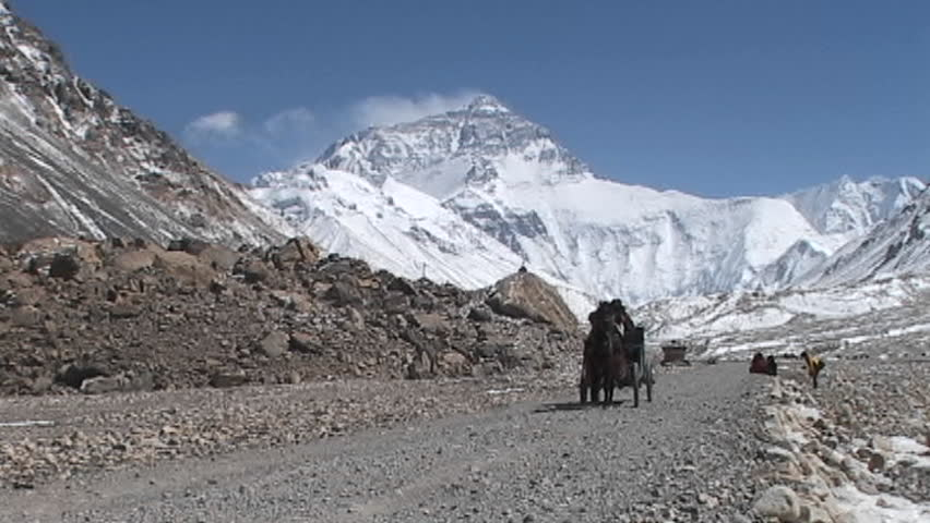 MOUNT EVEREST, NEPAL - CIRCA 2005: Tibetan men and climber ride in a carriage pulled by a horse near base camp circa 2005 on Mount Everest.
