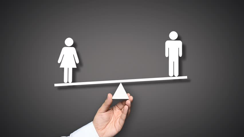 Gender equality concept. Hand holding balance with male and female figures. The female figure outweighs the male figure