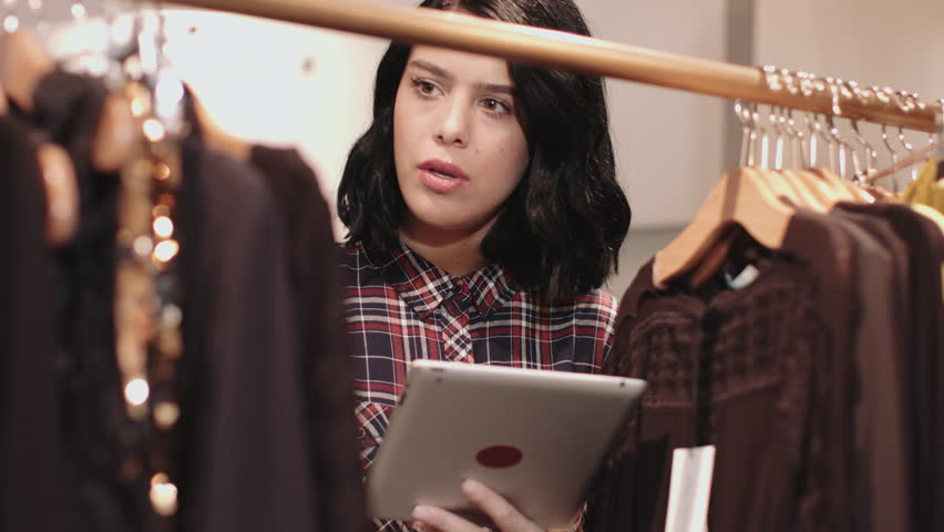 Small business owner in clothes shop ordering inventory on digital tablet