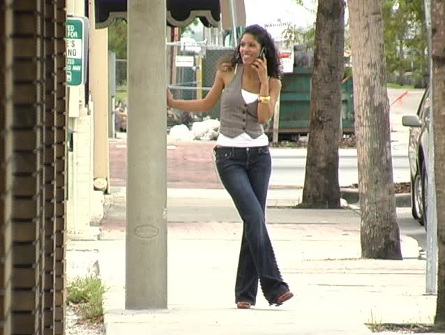 A beautiful Latina brunette walks toward the camera while talking on her cell phone.  Full-length.