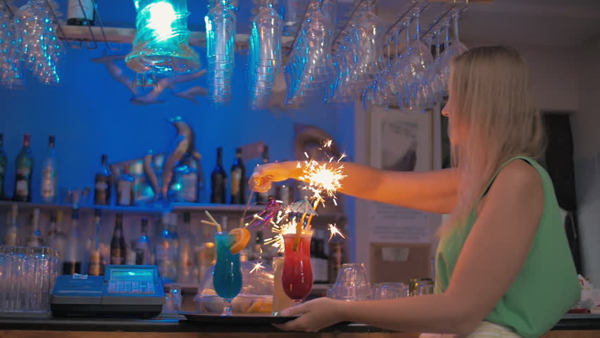 Slow motion steadicam shot of a young happy waitress setting on the Bengal fires in cocktails and carrying them through the bar #15518293
