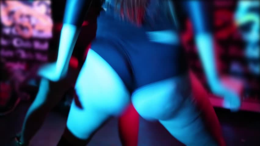 Close up booty woman dancing on stage of club next to other.