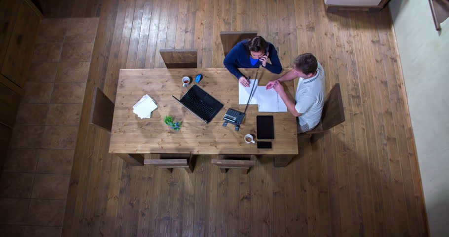 A middle-aged couple is working from home. They're checking their tablet, talking on the phone, they also have some paperwork to do. Wide-angle shot. | Shutterstock HD Video #15537709