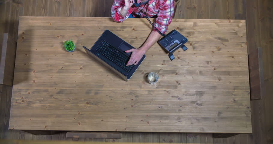 A young guy is typing something on his computer and then he is taking a phone call because it was ringing. Wide-angle shot. | Shutterstock HD Video #15539083